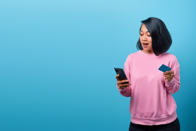 青い背景に携帯電話とクレジットカードを持って驚いた美しいアジアの女性