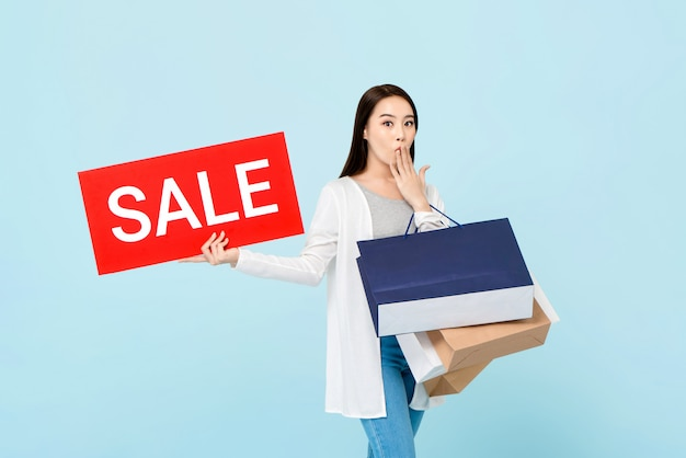 Surprised beautiful asian woman showing red sale sign