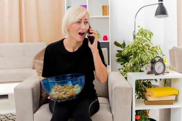 La bella donna russa bionda sorpresa si siede sulla poltrona che parla sul telefono che tiene una ciotola di patatine fritte all'interno del soggiorno Foto Gratuite