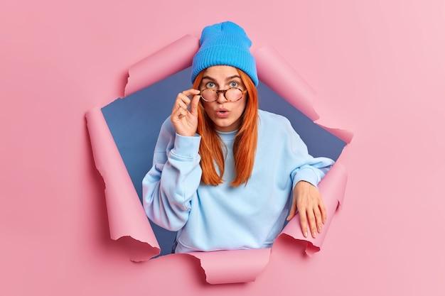 Sorpresa, bellissima femmina con i capelli rossi naturali tiene la mano sul bordo degli occhiali e guarda si sente sbalordita quando sente qualcosa di scioccante indossa abiti blu.