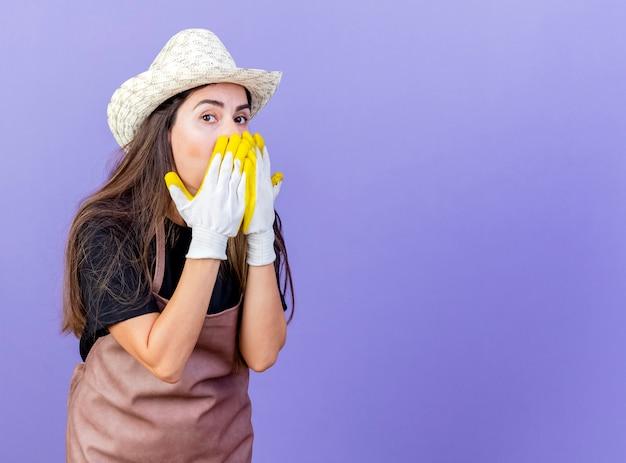 ガーデニングの帽子と手袋を身に着けている制服を着た驚いた美しい庭師の女の子は、コピースペースで青い背景に分離された手で顔を覆った