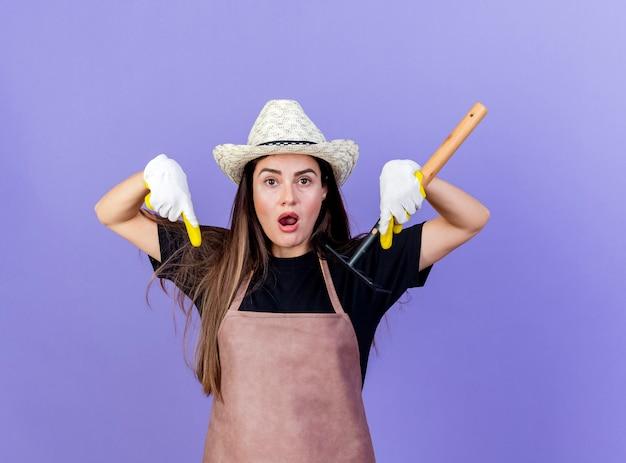 青い背景で隔離の熊手とポイントを保持している園芸帽子と手袋を身に着けている制服を着た驚いた美しい庭師の女の子