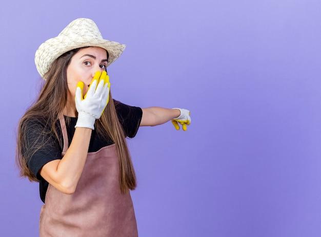 Удивленная красивая девушка-садовник в униформе в садовой шляпе и перчатках указывает на спину и кладет руку на рот, изолированный на синем