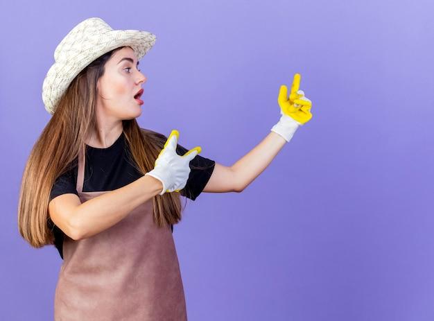 Удивленная красивая девушка-садовник в униформе в садовой шляпе и перчатках указывает сбоку, изолированную на синем