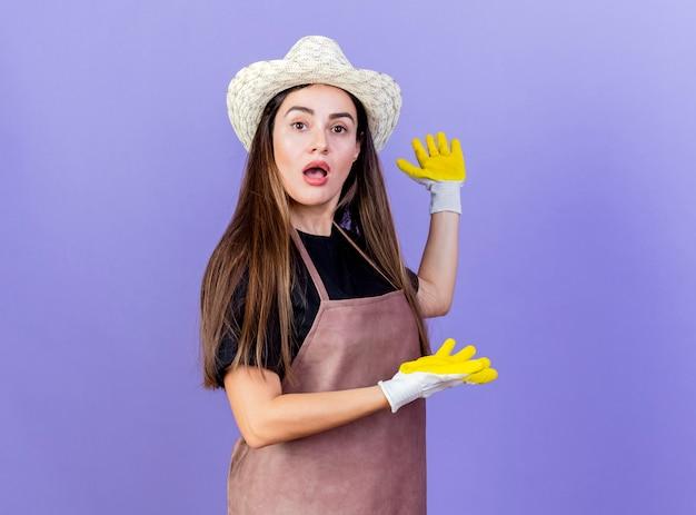 ガーデニングの帽子と手袋を身に着けている制服を着た驚いた美しい庭師の女の子は、青い背景で隔離の側に手をポイント