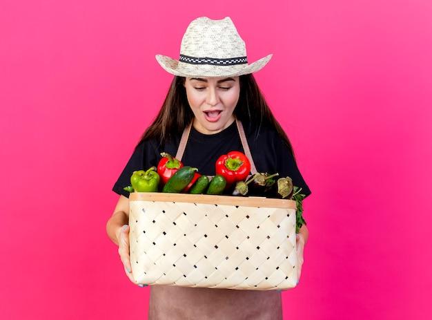Удивленная красивая девушка-садовник в униформе в садовой шляпе держит и смотрит на корзину с овощами, изолированную на розовом