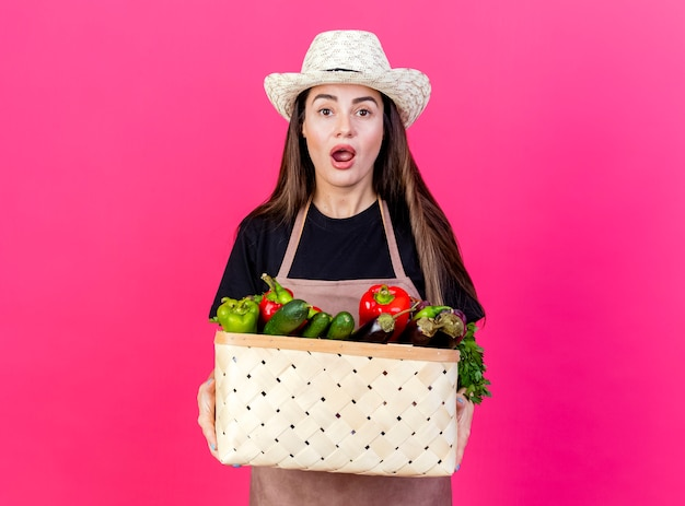 Удивленная красивая девушка-садовник в униформе в садовой шляпе держит корзину с овощами, изолированную на розовом