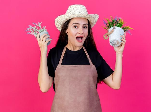 ピンクの背景に分離された植木鉢で花を育てるガーデニング帽子を身に着けている制服を着て驚いた美しい庭師の女の子