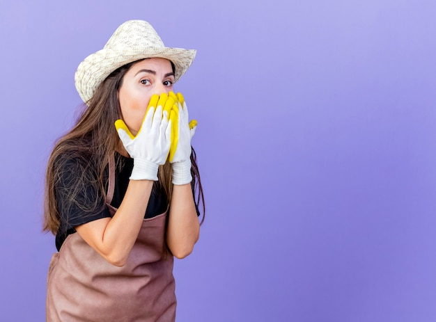 Sorpreso bella ragazza giardiniere in uniforme che indossa guanti e cappello da giardinaggio coperto il viso con le mani isolate su sfondo blu con copia spazio