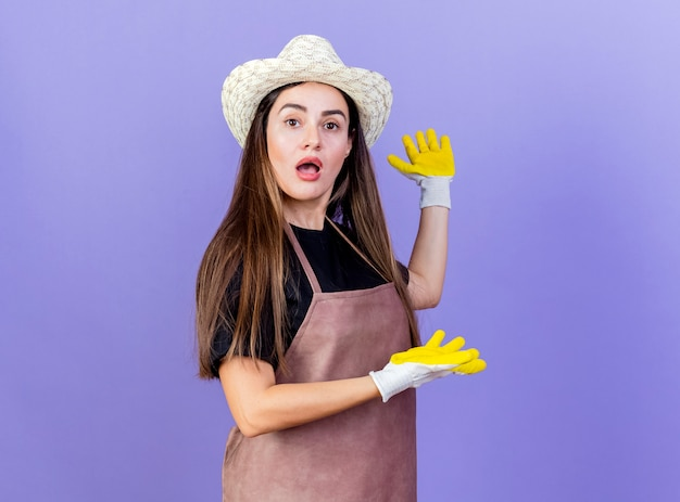 Sorpreso bella ragazza giardiniere in uniforme indossando guanti e cappello da giardinaggio punti con le mani a lato isolato su sfondo blu