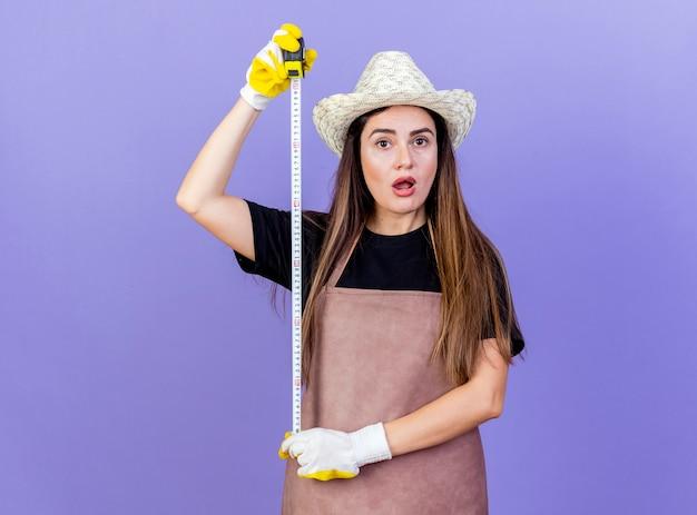 Bella ragazza sorpresa del giardiniere in cappello da giardinaggio d'uso uniforme e guanti che allungano la misura di nastro isolata sull'azzurro