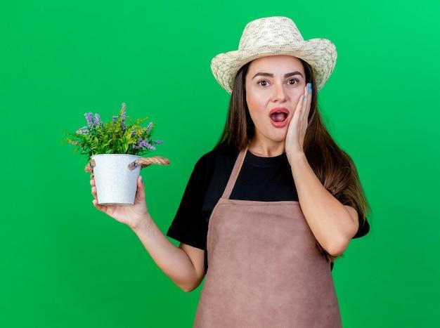 Sorpreso bella ragazza giardiniere in uniforme indossando cappello da giardinaggio tenendo il fiore in vaso di fiori e mettendo la mano sulla guancia isolato su sfondo verde