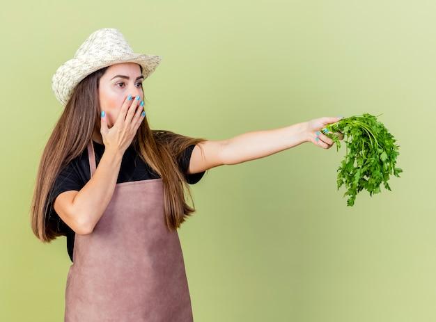 Sorpreso bella ragazza giardiniere in uniforme che indossa cappello da giardinaggio tenendo fuori il coriandolo a lato e la bocca coperta con la mano isolata su verde oliva