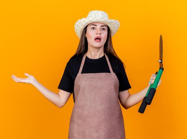 制服を着て、クリッパーズを保持し、オレンジ色の背景で隔離の手を広げてガーデニング帽子をかぶって驚いた美しい庭師の女の子