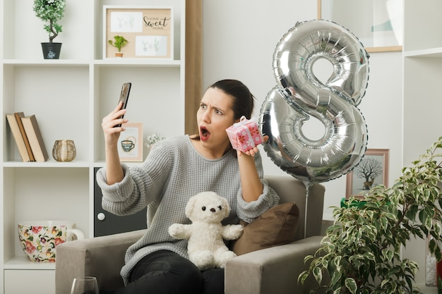 Surprised beautiful girl on happy women day holding present looking at phone in her hand sitting on armchair in living room