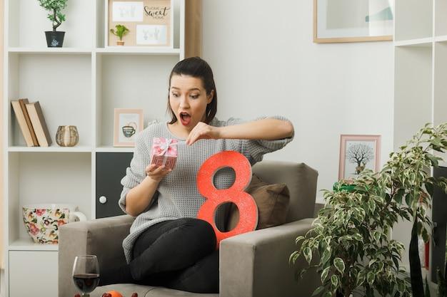 Удивленная красивая девушка в счастливый женский день держит и смотрит на настоящее, сидя на кресле в гостиной