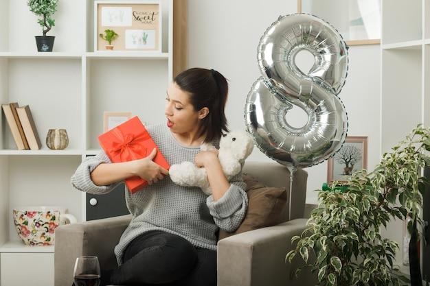 Удивленная красивая девушка в счастливый женский день держит и смотрит в настоящее время с плюшевым мишкой, сидящим на кресле в гостиной