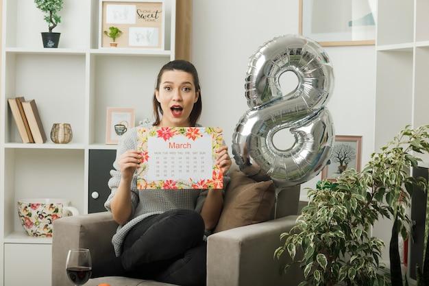 행복한 여성의 날 거실에 있는 안락의자에 앉아 달력을 들고 놀란 아름다운 소녀