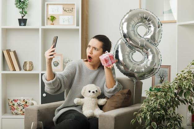 リビングルームの肘掛け椅子に座って彼女の手で携帯電話を見てプレゼントを保持している幸せな女性の日に驚いた美しい少女