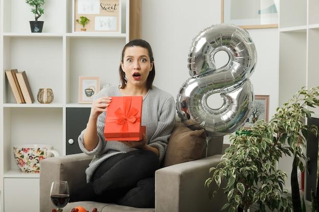 リビングルームの肘掛け椅子に座ってプレゼントを保持している幸せな女性の日に驚いた美しい少女