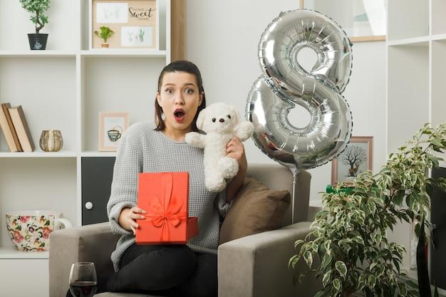 Удивленная красивая девушка в счастливый женский день держит подарок с плюшевым мишкой, сидящим на кресле в гостиной