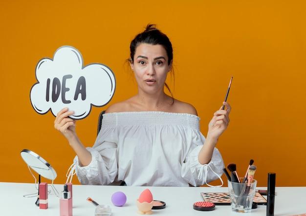 La bella ragazza sorpresa si siede al tavolo con gli strumenti di trucco che tengono il segno di idea e la spazzola di trucco isolata sulla parete arancione