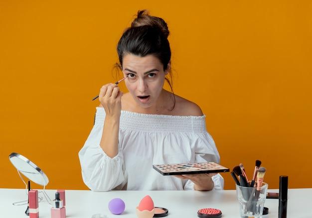 La bella ragazza sorpresa si siede al tavolo con gli strumenti di trucco tiene la tavolozza dell'ombretto che applica l'ombretto con la spazzola di trucco isolata sulla parete arancione