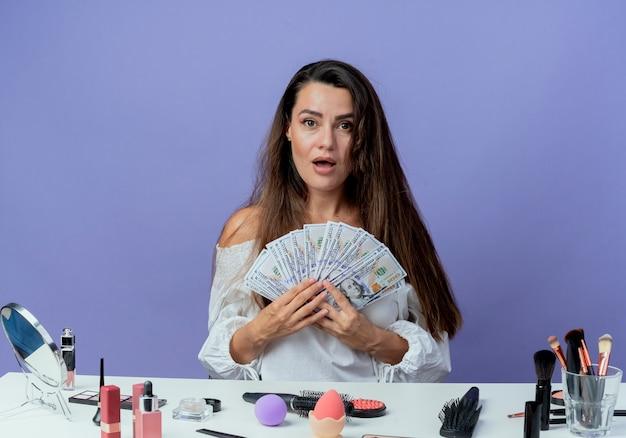 La bella ragazza sorpresa si siede al tavolo con gli strumenti di trucco tiene i soldi isolati sulla parete viola