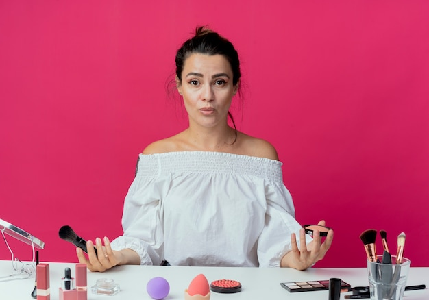 Surprised beautiful girl sits at table with makeup tools holds powder and makeup brush isolated on pink wall