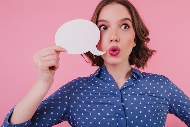 何かを考えて目をそらしているびっくりした美少女。ピンクの壁に感情を表現する見事な驚きのブルネットの女性。