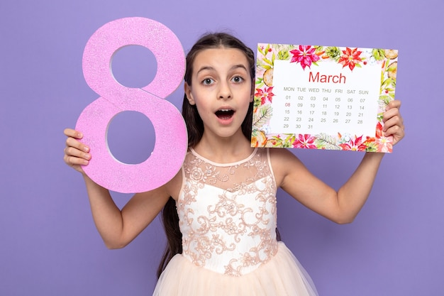 Surprised beautiful little girl on happy woman's day holding number eight with calendar around face isolated on blue wall