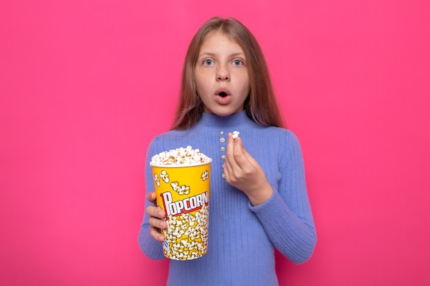 ポップコーンのバケツを保持している青いセーターを着て驚いた美しい少女
