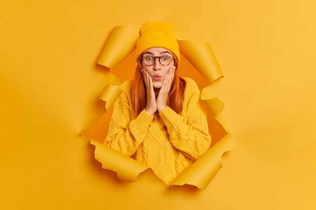 Surprised beautiful redhead woman keeps hands on cheeks sees something unbelievable stares wears yellow sweater and hat breaks through paper hole. astonished impressed female indoor