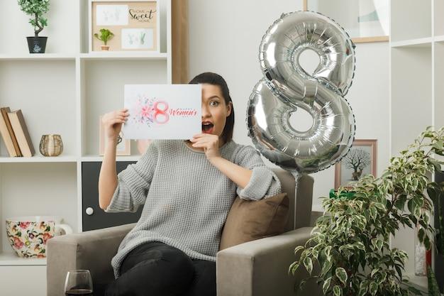 Bella donna sorpresa durante la giornata delle donne felici che tiene in mano e copre il viso con una cartolina seduta su una poltrona in soggiorno
