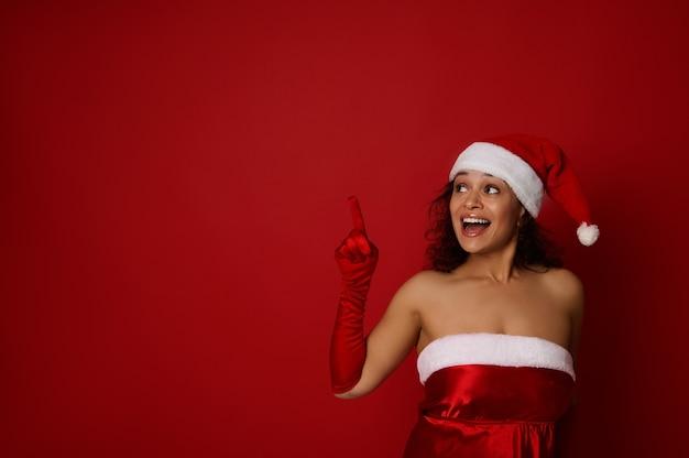 산타 카니발 의상을 입은 놀란 아름다운 여성은 아름다운 이빨 미소로 미소를 짓고 빨간색 배경의 복사 공간을 가리키며 올려다봅니다. 메리 크리스마스, 광고를 위한 새해 복 많이 받으세요 개념