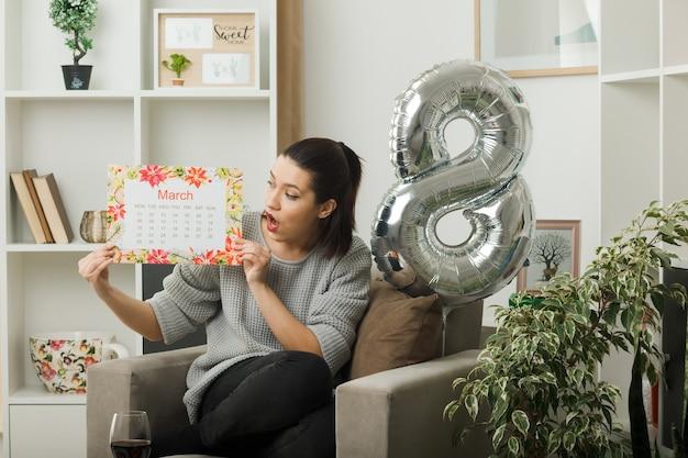 Удивленная красивая женщина в счастливый женский день держит и смотрит в календарь, сидя на кресле в гостиной