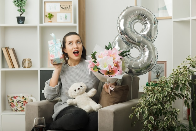 행복한 여성의 날 거실에 있는 안락의자에 꽃다발을 들고 선물을 들고 놀란 아름다운 여성