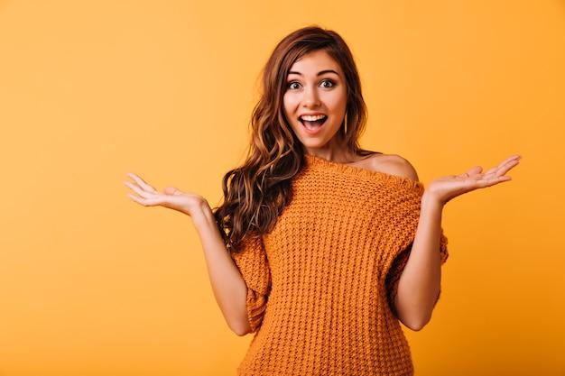 明るい黄色でポーズをとって驚いた美女。驚いた表情でスタジオに立っている素敵なブルネットの女の子。