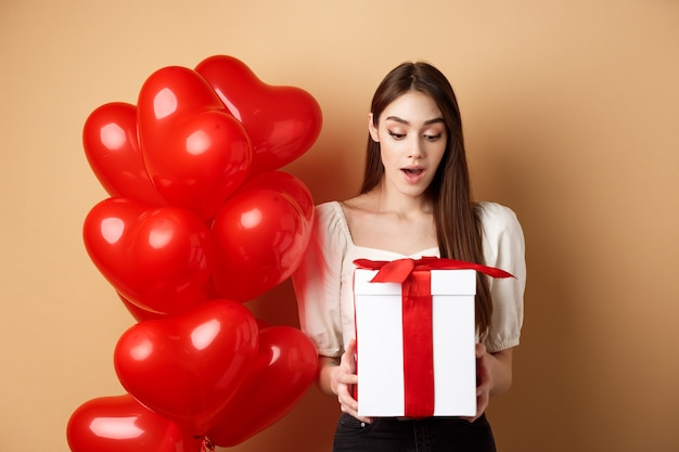 Surprised beautiful woman in romantic outfit, standing near heart balloons and looking at her gift on valentines day