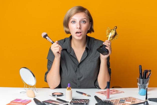 놀란 아름다운 여성은 화장용 브러시로 우승컵을 들고 화장 도구를 들고 테이블에 앉아 있다