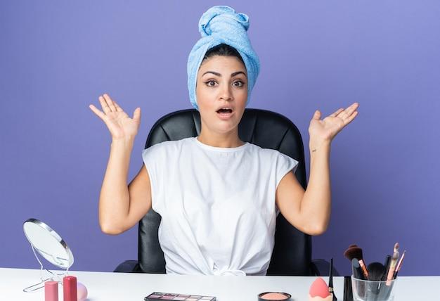 Удивленная красивая женщина сидит за столом с инструментами для макияжа, обернув волосы полотенцем, разводя руками