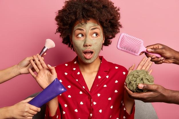 놀란 아름다운 여인이 빨간 잠옷을 입고 얼굴에 점토 마스크를 바르고 다양한 미용 제품을 향해 손바닥을 들어 올립니다.