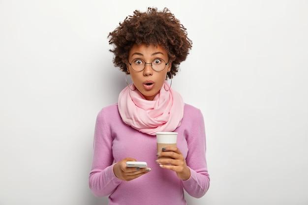 Удивленная красивая женщина с кудрявыми волосами просматривает ленту новостей, шокирована сообщением, держит кофе на вынос, не может во что-то поверить, носит оптические очки и фиолетовый свитер, позирует в помещении
