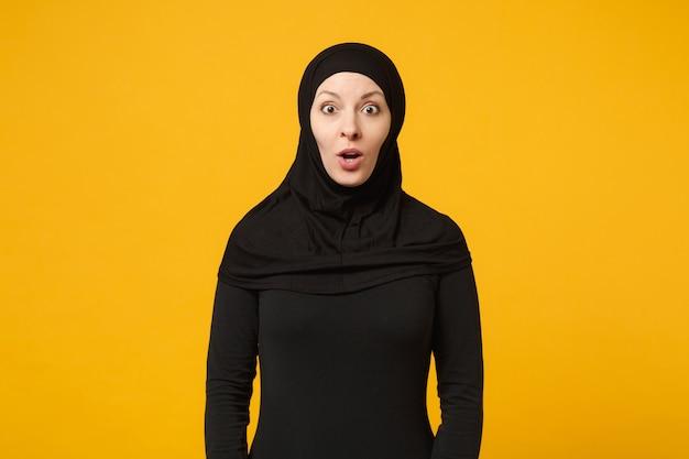 黄色の壁の肖像画に分離されたヒジャーブ黒のカジュアルな服を着て驚いた美しい若いアラビアのイスラム教徒の女性。人々の宗教的なライフスタイルの概念。
