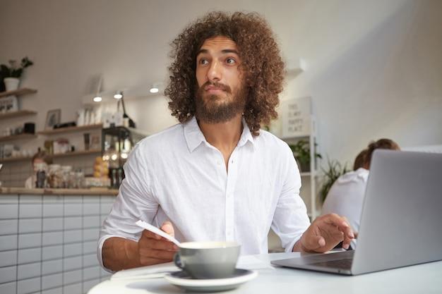 カフェのテーブルに座って、眉を上げて額を収縮させ、驚いて目をそらし、リモートで作業している白いシャツを着た驚いた美しい若いひげを生やした男