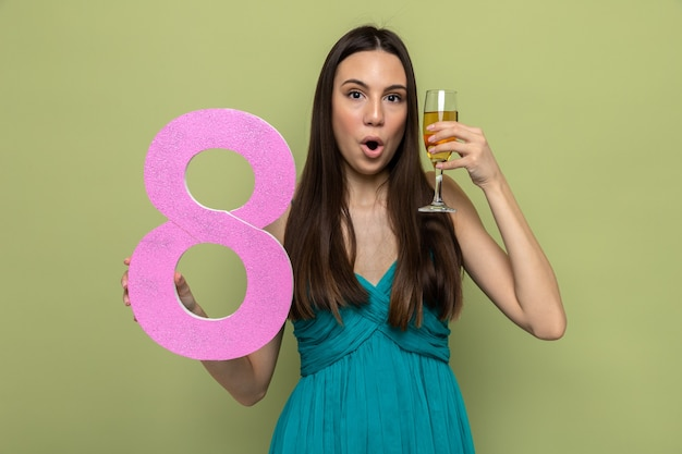 オリーブグリーンの壁に隔離されたシャンパングラスで8番を保持している幸せな女性の日に驚いた美しい少女