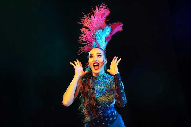 びっくり。カーニバルの美しい若い女性、ネオンの光の中で黒い背景に羽を持つスタイリッシュな仮面舞踏会の衣装。