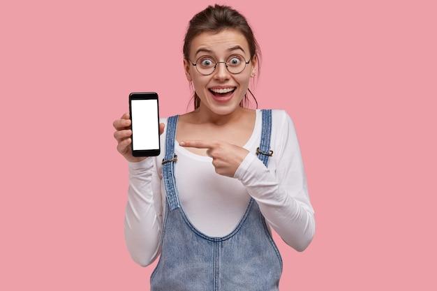 驚いた美しい若い女性は、スマートフォンの空白の画面で示し、ファッショナブルな服を着て、あなたの情報のためのスペースを示しています