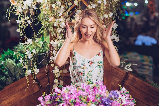 Surprised beautiful young woman looking at colorful flower bouquet in the garden