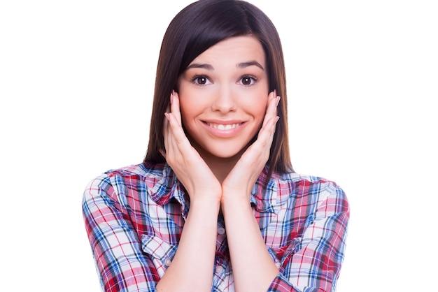 びっくりした美しさ。カメラを見て、白で隔離された状態で立っている間、手で彼女の顔に触れる美しい若い笑顔の女性